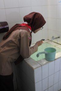 Mahasiswa melakukan pemeriksaan jentik nyamuk pada bak yang tergenang.